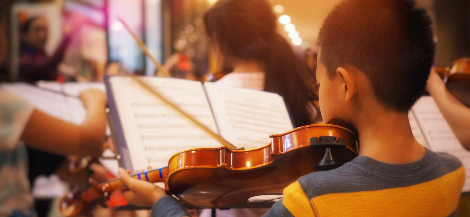 Young violinist practicing with orchestra band.